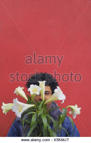 Man, young, swarthily, face,  Flower bouquet, covers, portrait  Men's portrait, 20-30 years, glasses bearers, Sehhilfe, dark-haired, hair, hairdo, curls, frill, hair frill, gaze camera gift bouquet flowers lilies, king lilies, Lilium shelves, background, - Stock Photo