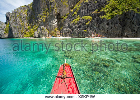 Outrigger boat off the steep limestone coast of Tapiutan Island, Bacuit archipelago, El Nido, Palawan, Philippines, Asia - Stock Photo