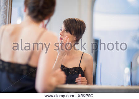 Woman applying anti-aging cream on her face - Stock Photo