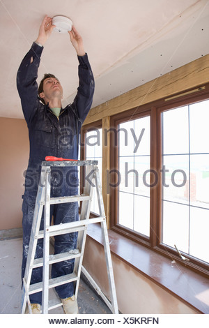 Man on ladder installing smoke detector - Stock Photo