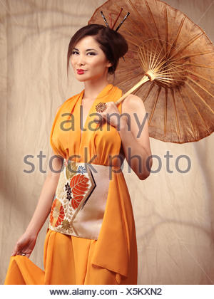 Woman wearing an orange dress holding an Asian parasol - Stock Photo
