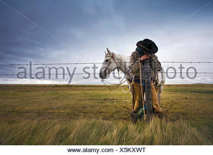 A cowboy standing leaning on a fence post on the range. A grey horse behind him.