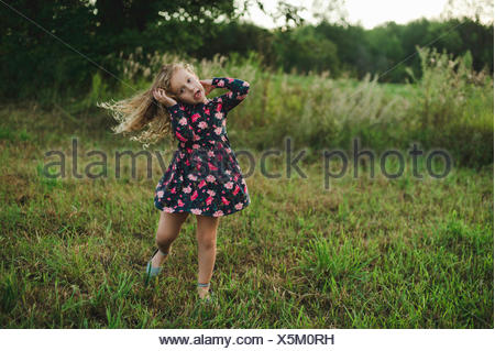 Blond haired girl running and pulling a face in field - Stock Photo