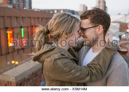 Couple hugging face to face on urban rooftop - Stock Photo
