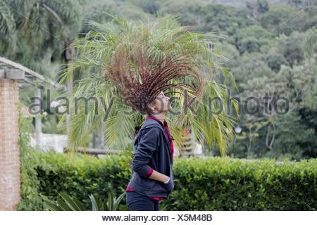 Woman With Tousled Hair Standing Against Trees - Stock Photo