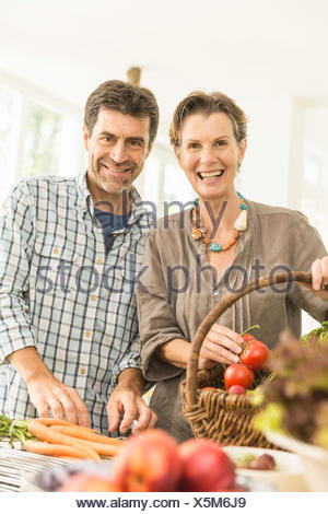 Portrait of couple preparing fresh vegetables in kitchen - Stock Photo