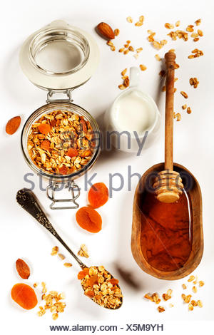 Homemade granola (with dried fruit and nuts) and healthy breakfast ingredients - honey, milk and fruits on white background - Stock Photo
