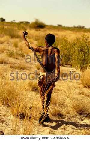 Bushman Walking Through Kalahari Desert, Botswana, Africa - Stock Photo