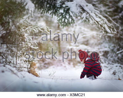 Baby boy playing in the snow with a teddy bear - Stock Photo