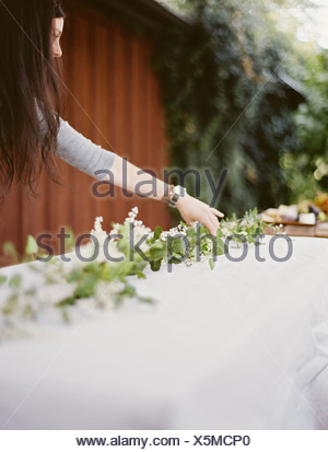 A woman with long hair by table laid outside with a white cloth and central foliage table decoration Place settings - Stock Photo