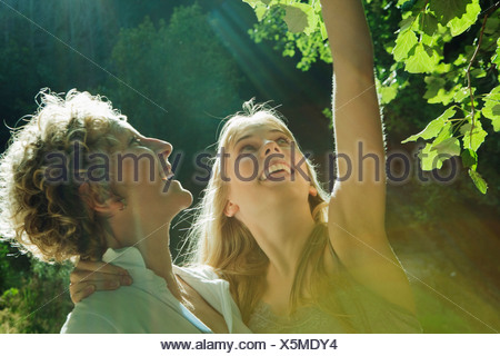Mother and daughter looking at tree - Stock Photo