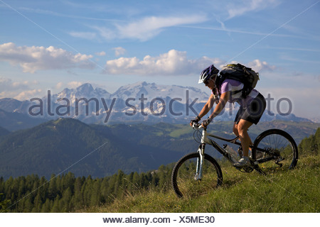Mountain bike rider on single trail at Mt. Kreuzkofel, in the back Mt. Marmolada, Naturpark Fanes-Sennes-Prags, Trentino, South - Stock Photo