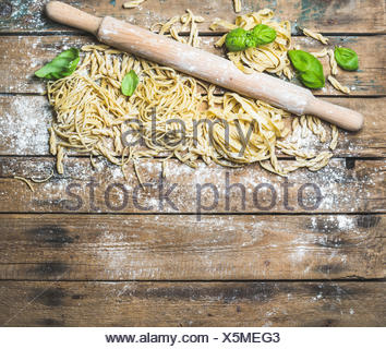 Various homemade fresh uncooked Italian pasta with flour, green basil leaves and plunger on shabby rustic wooden background, top - Stock Photo