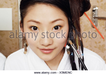 Portrait of a young woman applying make-up on her face - Stock Photo