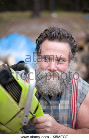 Crazed looking man with chainsaw. - Stock Photo