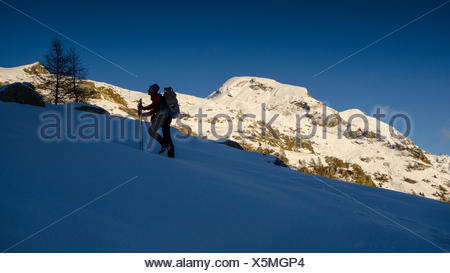 An hiker in silhouette, climbing a snowy slope. (Val d'Ayas, Vallée d'Aoste, Italy) - Stock Photo