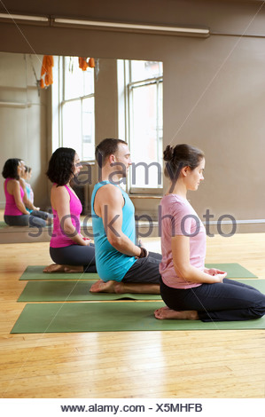 People kneeling in yoga class - Stock Photo