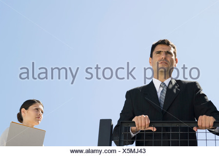 Businessman gripping railing and looking in the distance, assistant standing nearby - Stock Photo