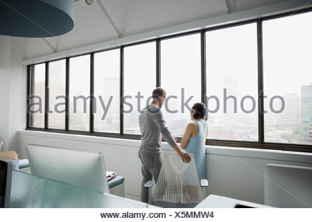 Architects looking out office window - Stock Photo