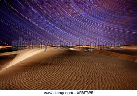 Star trails in the sky above the desert. - Stock Photo