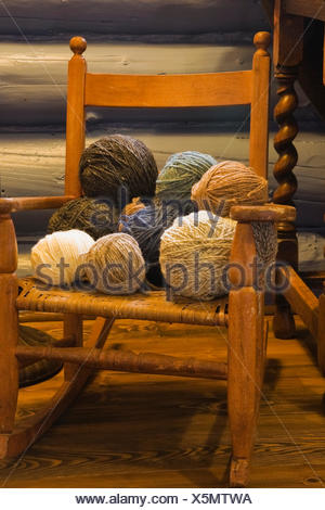 Balls of wool on small old wooden rocking chair in bedroom of country cottage style residential log home, Quebec, Canada - Stock Photo
