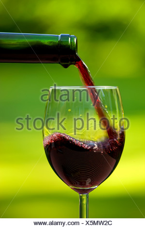 Close-up of red wine being poured in glass against blurred green background Stock Photo