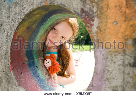 young girl peeking through hole in wall on playground - Stock Photo