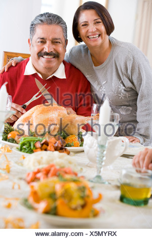Woman With Her Arm Around Her Husband, Who Is Getting Ready To Carve A Turkey - Stock Photo