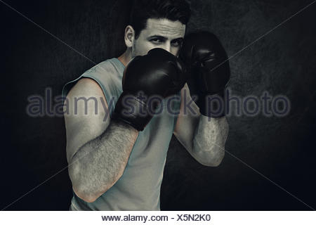 Composite image of determined male boxer focused on his training - Stock Photo