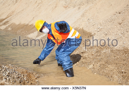 Germany, Bavaria, Man in protective workwear searching in water stream - Stock Photo