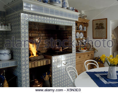 Lighted fire in blue+white tiled fireplace in eighties kitchen dining room - Stock Photo
