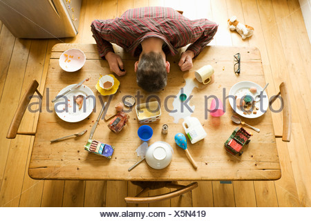 Overhead view of breakfast table with mature man amongst messy plates - Stock Photo
