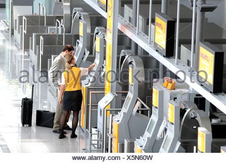 Lufthansa employee explaining to a passenger the Quick-Check-in-Terminal of Lufthansa, Terminal 2 of Munich Airport, Franz-Jose - Stock Photo