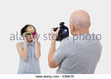 Senior photographer taking a photograph of fashion model during photo shoot - Stock Photo