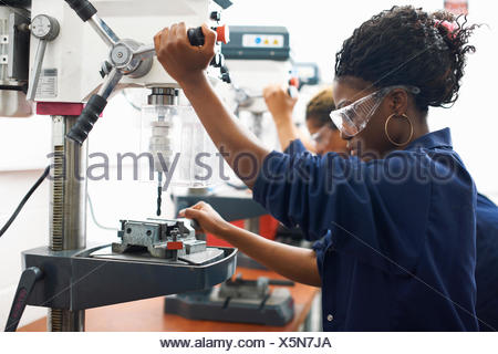 Students using drilling machines in college workshop