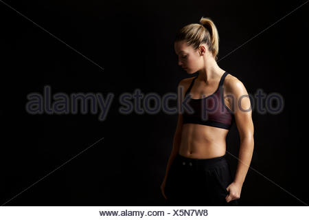 Portrait of a blonde woman in sports clothing looking down - Stock Photo