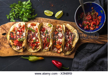 Shrimp tacos with homemade salsa sauce, limes and parsley on wooden board over dark background. Top view. Mexican cuisine - Stock Photo