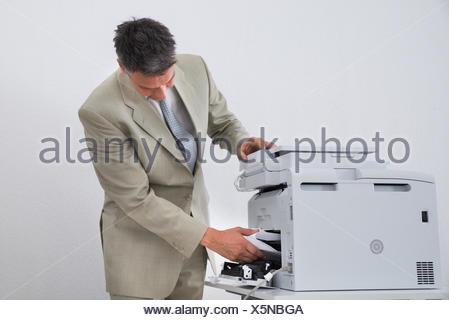 Businessman Removing Paper Stuck In Printer - Stock Photo