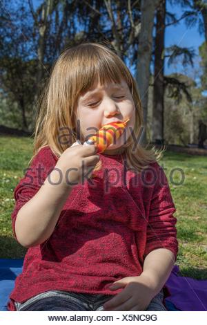 portrait of three years old blonde child, eating enjoying colorful orange and red ice lolly or popsicle, sitting on green grass field in public park - Stock Photo