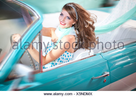 Woman with windblown hair driving vintage convertible - Stock Photo