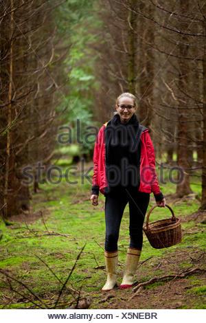junge frau mit roter jacke im herbst sammelt pilze im wald natur entspannung lebensmittel - Stock Photo