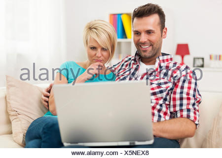 Young couple watching something on computer - Stock Photo