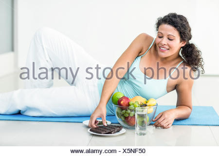 Pregnant woman about to hold chocolate bar - Stock Photo