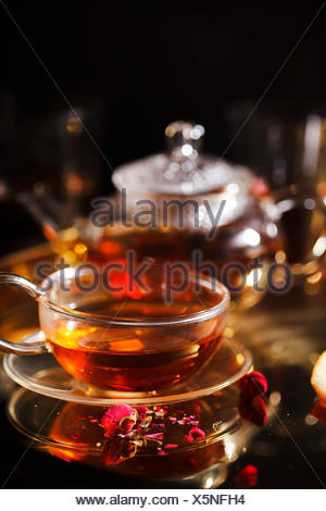 Vertical close-up shot of small glass teapot and cup with hot red tea, dried rose petals, pocket magnifier on golden chain on golden tray. Evening lig - Stock Photo