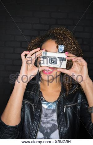 Portrait of woman using retro camera - Stock Photo