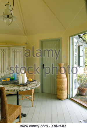 Tall, Wicker Vase Beside Doorway In Pale Yellow Dining Room With Painted  Floorboards   Stock