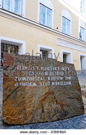 Memorial stone against war and fascism in front of the birth place of Adolf Hitler Braunau upon the river Inn Upper Austria - Stock Photo