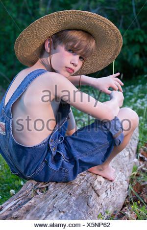 Young boy wearing overalls sitting on tree wearing straw hat - Stock Photo