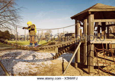 Little boy walking along a hanging bridge on a playground - Stock Photo
