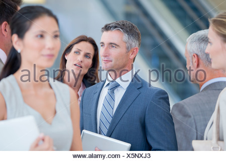 Serious businessman listening to co-worker - Stock Photo